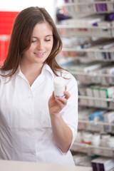 Female Pharmacist Reading Information On Medicine