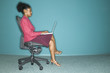 Profile of businesswoman sitting in chair with laptop