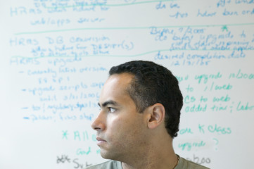 Profile of man in front of white board