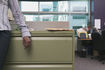 Midsection businessman leaning on filing cabinet