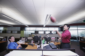 Two businessmen playing catch with football
