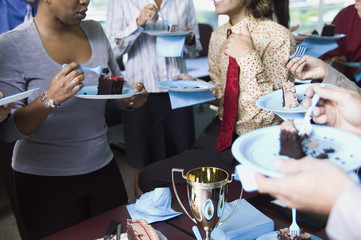 Business people eating cake