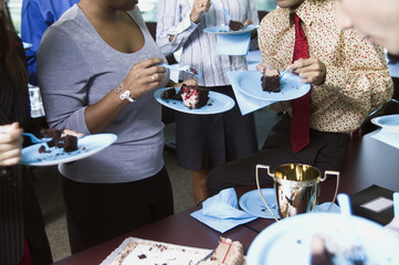 Midsection of businesspeople eating cake