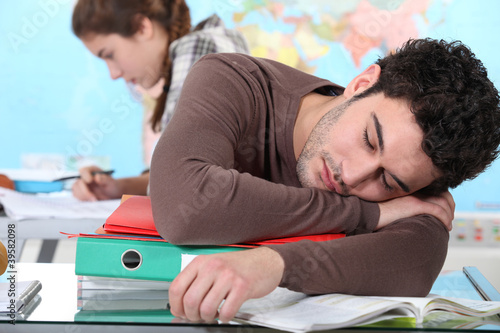 Young man sleeping during a university lecture
