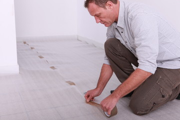 Man taping down underlay