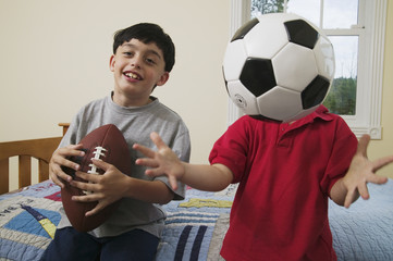 Portrait of brothers with soccer ball and football