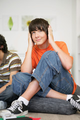 Teens relaxing on the sofa with music