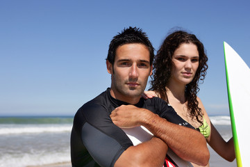 Couple stood on the beach with surf boards