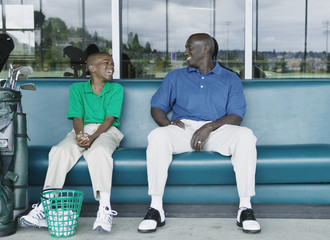 Father and son laughing at driving range