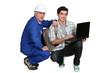 A tradesman helping his apprentice write a report