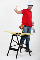 Confident laborer with saw