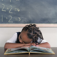 School girl sleeping on book
