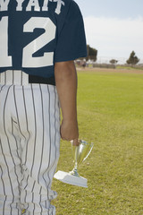 Young baseball player holding trophy