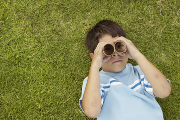 Young boy looking through toy binoculars
