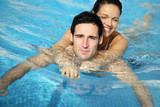 Man and woman embraced in swimming pool