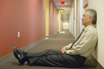 Businessman sitting on floor of hallway