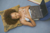 Young woman using laptop on stomach