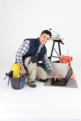Tile cutter kneeling by laptop computer