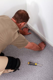 Man fitting carpet into the corner of a room