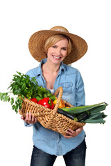 Blond carrying a basket full of vegetables.