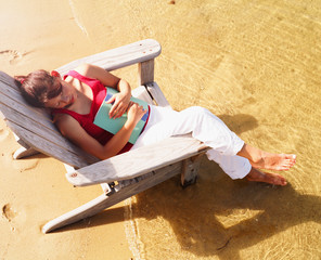 High angle view of a young woman sitting on a beach chair