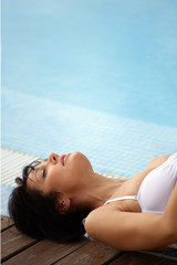 Brunette having a nap by swimming pool