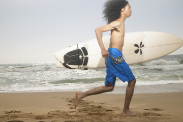 Young man running along beach with surfboard