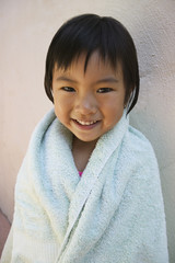 Young girl smiling wrapped up in towel