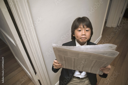 Young boy reading newspaper comically