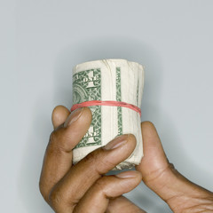 Close up of hand holding roll of dollar bills