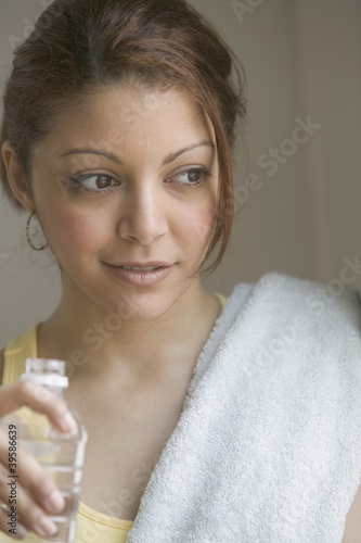 Woman with water bottle and towel