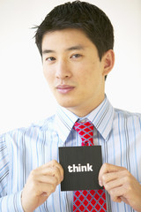 """Portrait of businessman holding """"think"""" sign"""