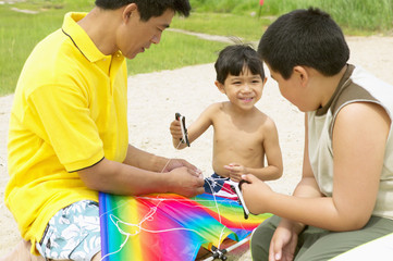 Father and sons flying kite