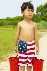Boy carrying buckets at beach
