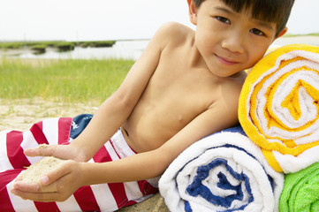 Boy laying on towels at beach