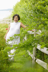 Pregnant woman standing by fence