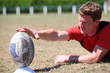 Man preparing rugby ball for kick