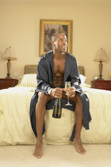Man in robe with champagne in bedroom