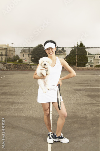 Woman playing tennis and holding dog