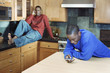 Brothers talking on cell phones in kitchen