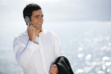 Businessman making call at the beach