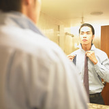 Businessman looking in mirror to pick tie