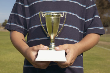 Midsection of boy holding trophy