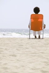 Rear view of woman sitting on beach