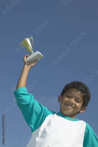 Portrait of boy holding trophy