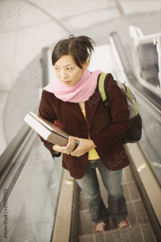 High angle view of woman riding escalator