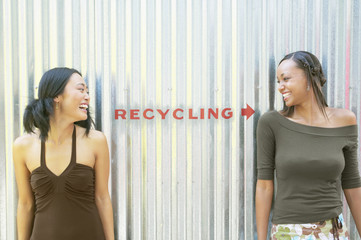Two female friends standing by recycling sign