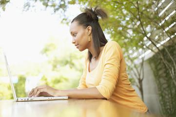 Profile of teenage girl typing on laptop