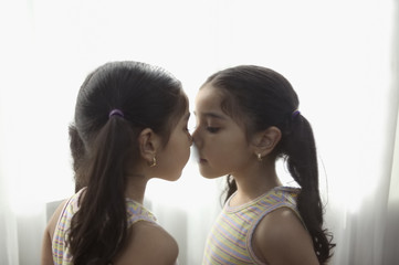 Girl touching nose to mirror