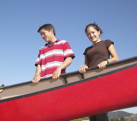 Portrait of teenagers carrying canoe